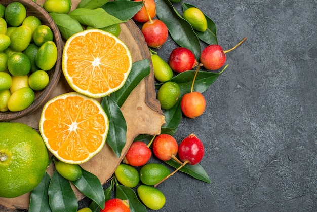 Top close-up view fruits the cutting board with citrus fruits with leaves and cherries
