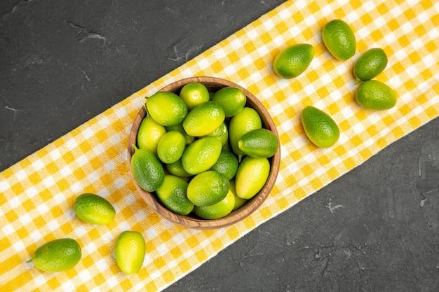 暗いテーブルの上の白黄色のテーブルクロスのボウルの上のクローズアップビューフルーツフルーツ