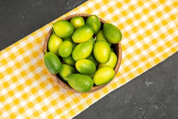 テーブルの中央にある白黄色のテーブルクロスの上のクローズアップビューフルーツフルーツ