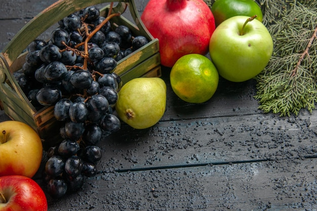 Top close-up view fruits grapes in wooden box apples pomegranate pears limes next to spruce branches on dark table