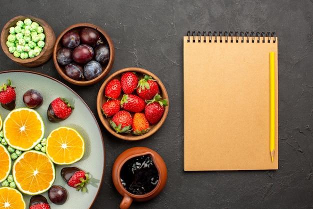 Вид сверху крупным планом фрукты, зеленые конфеты, клубника в шоколаде, нарезанный апельсин и миски с ягодами и шоколадным соусом рядом с блокнотом и карандашом