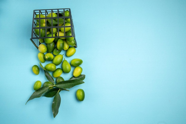 Top close-up view fruits green citrus fruits with leaves in the grey basket on the blue table