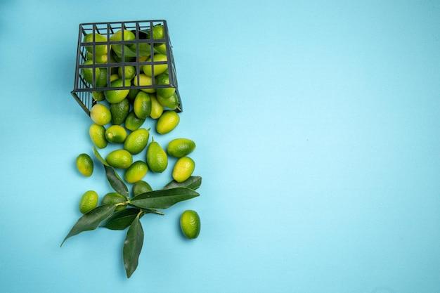 파란색 탁자에 있는 회색 바구니에 잎이 있는 녹색 감귤류 과일