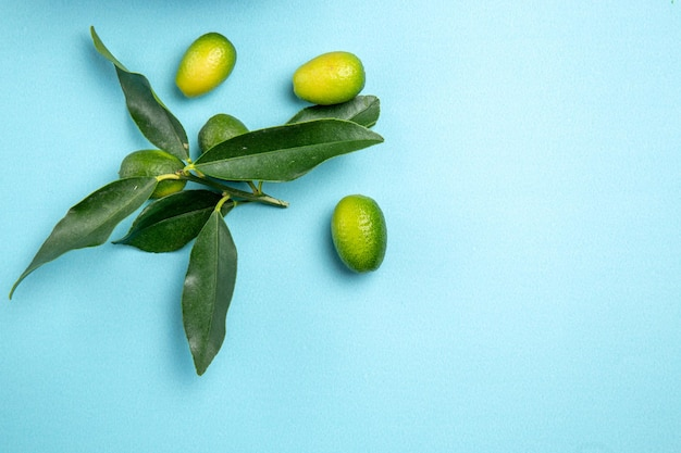 上のクローズアップビューフルーツ青いテーブルの上に葉を持つ緑の柑橘系の果物