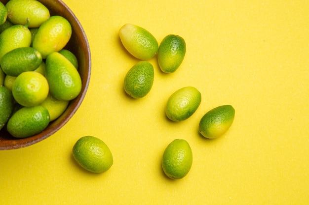 노란색 탁자에 있는 위쪽 클로즈업 보기 과일 녹색 과일과 갈색 그릇