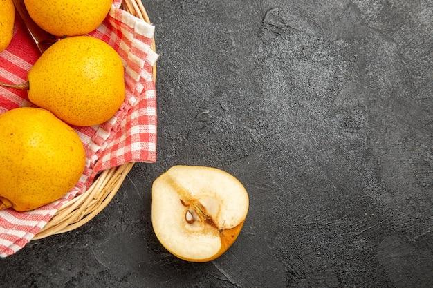 バスケットのテーブルクロスの洋ナシと暗いテーブルの半分の洋ナシを食欲をそそるバスケットの上部のクローズアップビューの果物