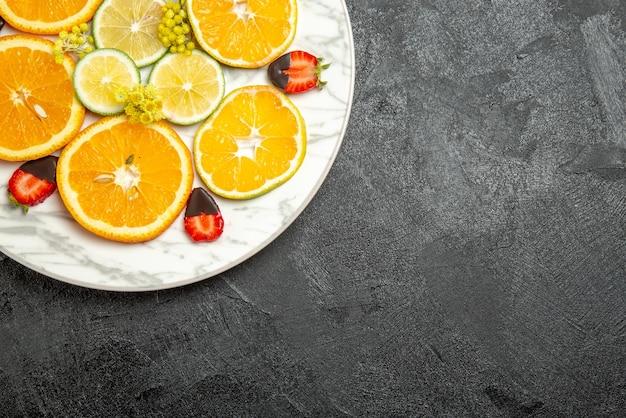 테이블 왼쪽에 있는 흰색 접시에 초콜릿으로 덮인 딸기 슬라이스 레몬 오렌지