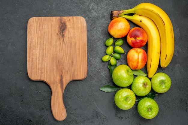 Сверху крупным планом фрукты на разделочной доске стола рядом с яблоками, бананами и нектаринами