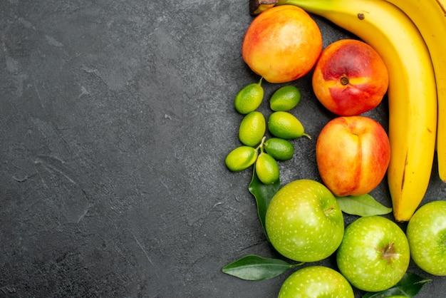 テーブルの上のクローズアップビューの果物は、黄色いバナナとネクタリンの葉と青リンゴをライムします