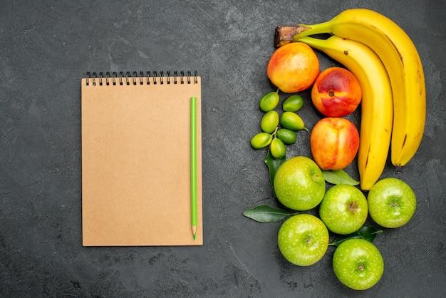 Сверху крупным планом фрукты на столе тетрадь карандашом рядом с яблоками, бананами и нектаринами