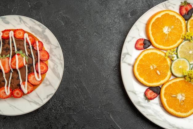 Frutti di vista ravvicinata dall'alto sul piatto della torta con cioccolato e fragole e piatto di agrumi e fragole ricoperte di cioccolato