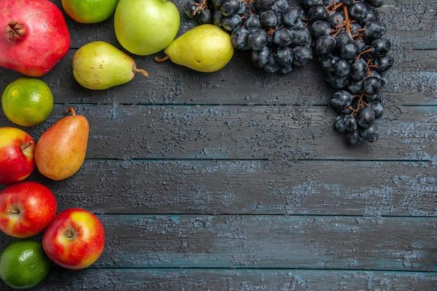 위쪽 클로즈업 보기 과일 석류 사과 배 라임과 포도는 어두운 탁자에 원 안에 놓여 있습니다
