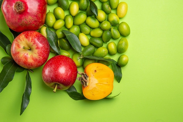 Top close-up view fruits pomegranates apples green citrus fruits persimmons on the table