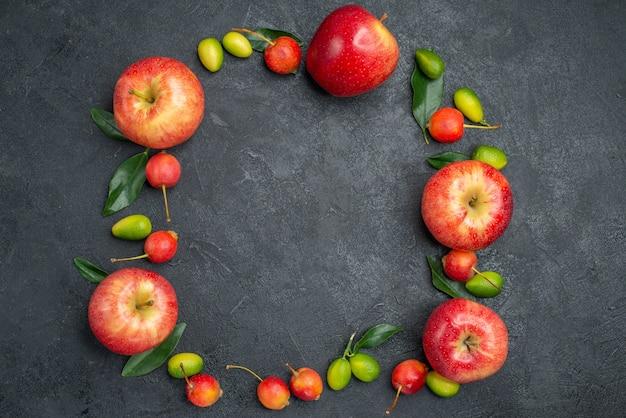 Vista ravvicinata dall'alto frutti mele rosse ciliegie agrumi sono disposti in un cerchio