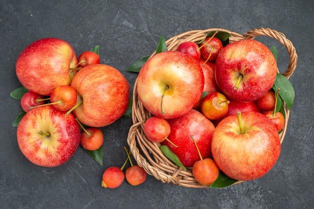 Вид сверху крупным планом фрукты красно-желтые яблоки и ягоды с листьями в корзине