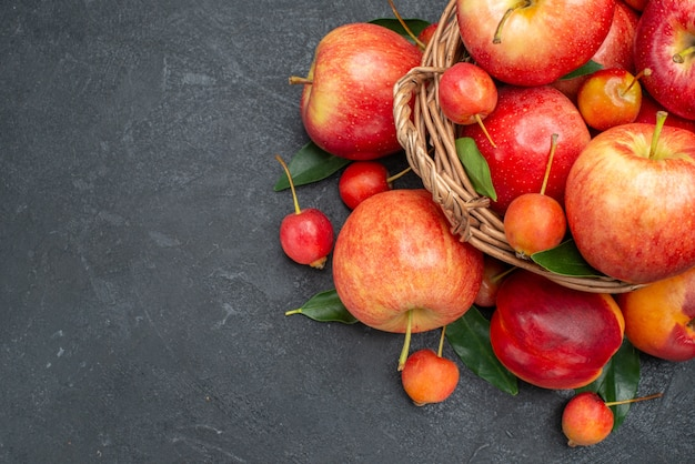 Вид сверху крупным планом фрукты красно-желтые фрукты и ягоды с листьями в корзине