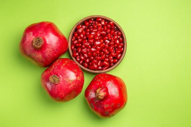 Вид сверху крупным планом фрукты семена граната аппетитные яблоки на зеленой поверхности