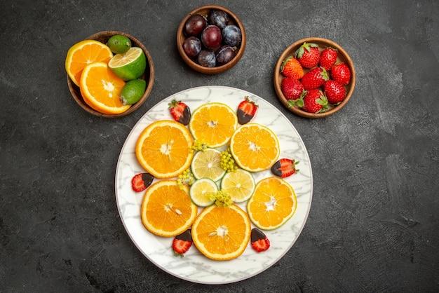 Vista ravvicinata dall'alto frutti sul tavolo fragole ricoperte di cioccolato limone e arancia in piatto bianco accanto ad agrumi e bacche in ciotole al centro del tavolo scuro