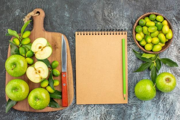 上部のクローズアップビューフルーツボード上の食欲をそそるリンゴナイフ柑橘系の果物ノートブック鉛筆