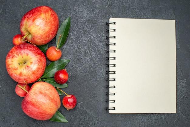 Вид сверху крупным планом фрукты, аппетитные ягоды и фрукты с листьями ноутбука