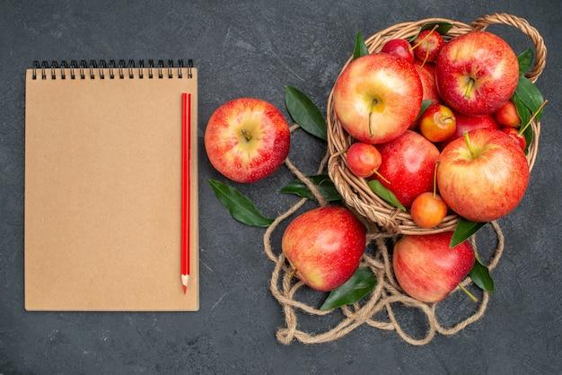 Сверху крупным планом фрукты аппетитные вишни и яблоки в корзине тетрадь карандашом
