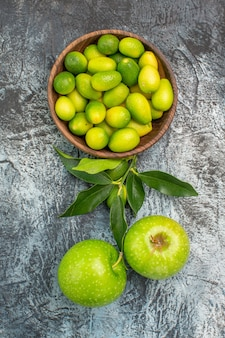上部のクローズアップビューは、ボウルに食欲をそそる柑橘系の果物と2つのリンゴを実らせます