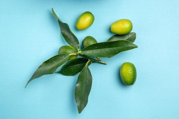 上のクローズアップビューは青いテーブルの上に葉を持つ食欲をそそる柑橘系の果物を果物します