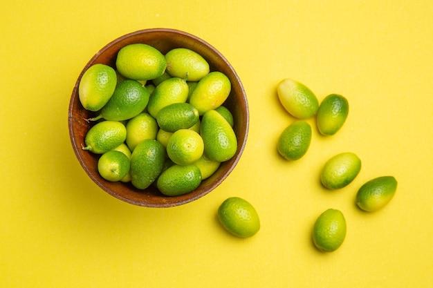 上部のクローズアップビューは、黄色いテーブルのボウルの横にある食欲をそそる緑色の果物を果物します