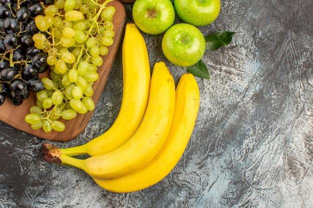 상위 클로즈업 보기 과일 3개의 바나나 사과 녹색 및 검은색 포도가 부엌 보드에 있습니다.