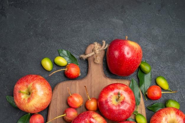 Вид сверху крупным планом фрукты желто-красные ягоды яблоки на доске цитрусовые
