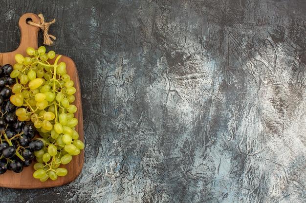 テーブルの上の木製のまな板の上にブドウを食欲をそそる上部のクローズアップビューブドウ