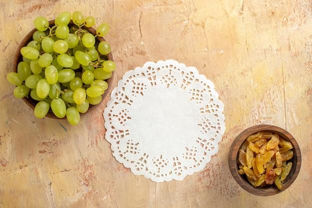 上部のクローズアップビューレーズンと緑のブドウのブドウのボウルはテーブルの上でドイリーをひもで締めます