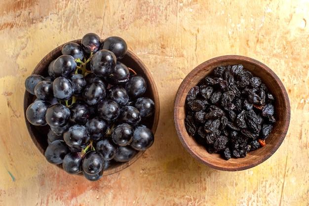 Vista ravvicinata superiore dell'uva ciotole di uvetta e uva nera sul tavolo
