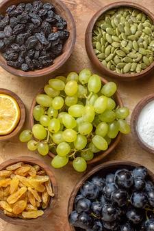 Top vista ravvicinata uva grappoli di uva nera e verde uva passa zucchero limone semi di zucca