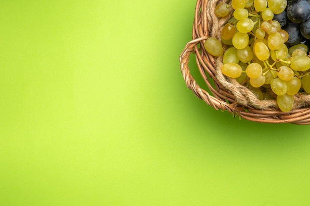 Vista ravvicinata dall'alto grappoli d'uva nel cesto di legno sullo sfondo verde