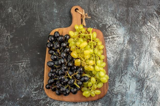 ボード上の緑と黒のブドウのブドウの房の上部のクローズアップビュー