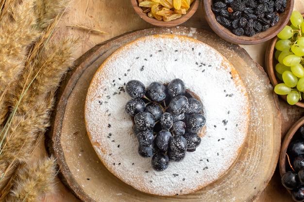 Top vista ravvicinata uva una torta con ciotole d'uva di spighette di uva passa uva nera e verde