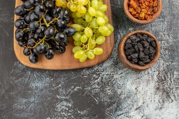 위쪽 클로즈업 보기 포도 말린 과일, 맛있는 포도 다발이 있는 커팅 보드