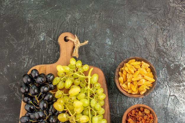 上部のクローズアップビューブドウボード上のおいしいブドウの食欲をそそるドライフルーツの束