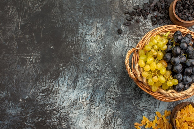 Вид сверху крупным планом на виноград аппетитный виноград между мисками с сухофруктами с правой стороны