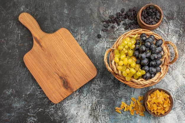 Вид сверху крупным планом виноград аппетитный виноград между мисками с сухофруктами на разделочной доске