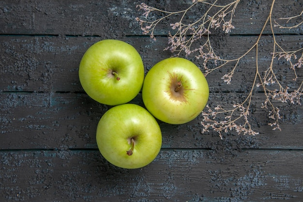 Vista ravvicinata dall'alto mele verdi tre mele appetitose accanto ai rami degli alberi al centro del tavolo grigio