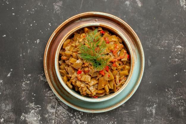 어두운 탁자에 있는 그릇에 토마토를 넣은 녹색 콩과 토마토 녹색 콩