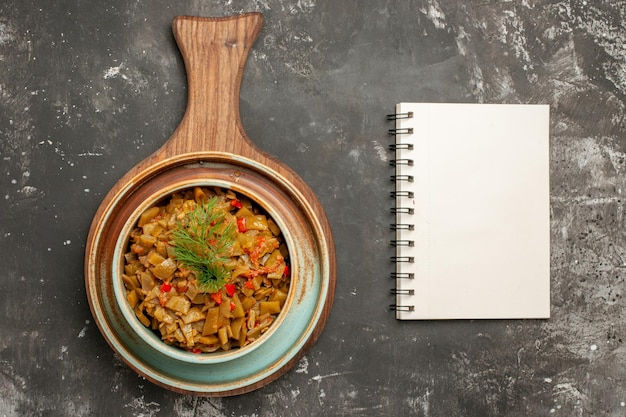Вид сверху крупным планом зеленая фасоль миска аппетитных помидоров зеленая фасоль на кухонной доске рядом с белой записной книжкой на черном фоне