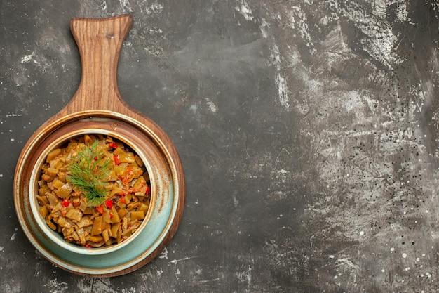 黒の背景の左側にあるキッチンボード上の食欲をそそるトマトサヤインゲンの上部のクローズアップビュー緑豆ボウル