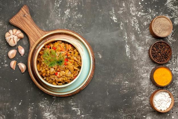 Vista ravvicinata dall'alto piatto di fagiolini dei fagiolini con pomodori sulla tavola aglio e cinque ciotole di spezie sul tavolo scuro