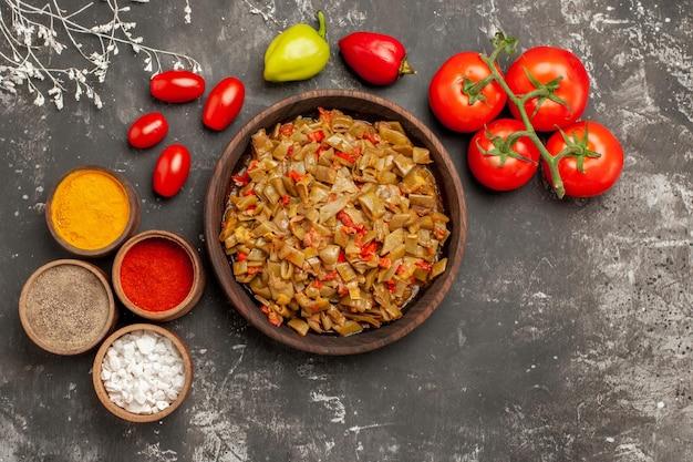 Vista ravvicinata dall'alto fagiolini e spezie fagiolini accanto alle ciotole di spezie colorate pomodori con pedicello e peperoni sul tavolo