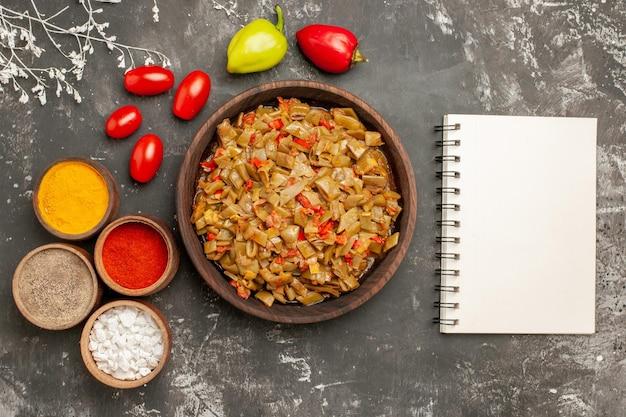 Vista ravvicinata dall'alto fagiolini e spezie fagiolini nel piatto spezie colorate pomodori e peperoni accanto al quaderno bianco sul tavolo
