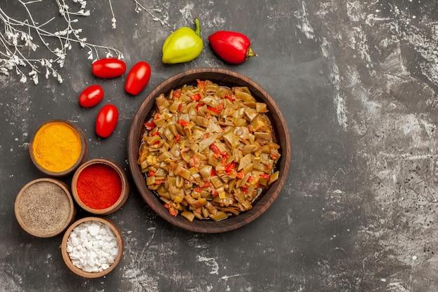 Vista ravvicinata dall'alto fagiolini e spezie fagiolini nel piatto quattro tipi di spezie pomodori e peperoni sul tavolo