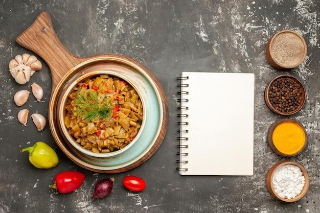 Vista ravvicinata dall'alto fagiolini quaderno bianco piatto dei fagiolini con pomodori sulla tavola peperoni cipolla aglio quaderno bianco e ciotole di spezie sul tavolo scuro